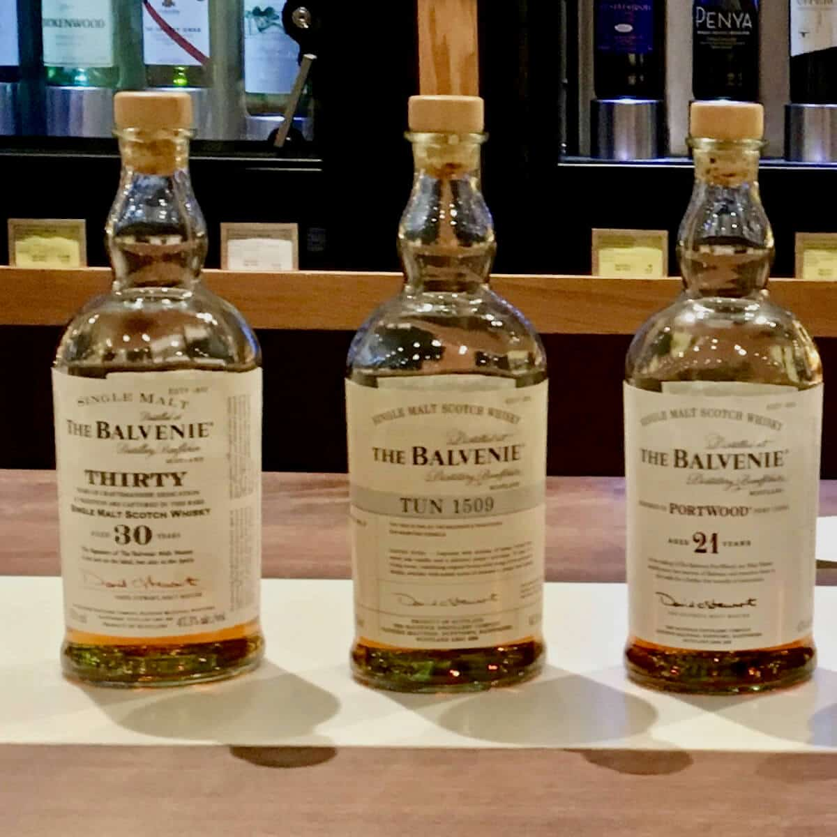 The Balvenie 21 year, Tun 1509, and 30 year lineup bottles on a counter.