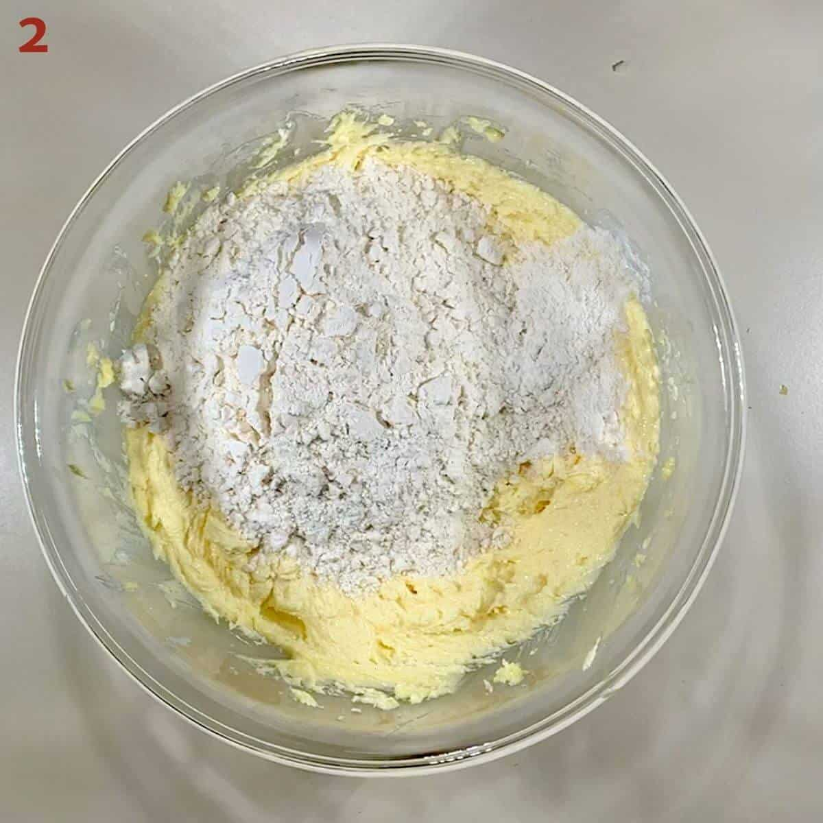 Adding flour to blended butter & sugar in a glass bowl.