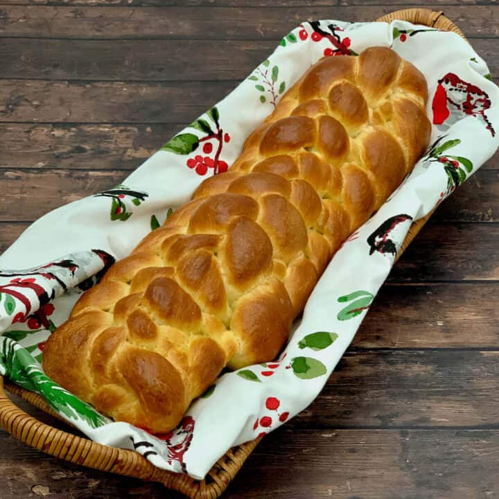 Eight strand braided challah in a napkin lined basket on a wood table.
