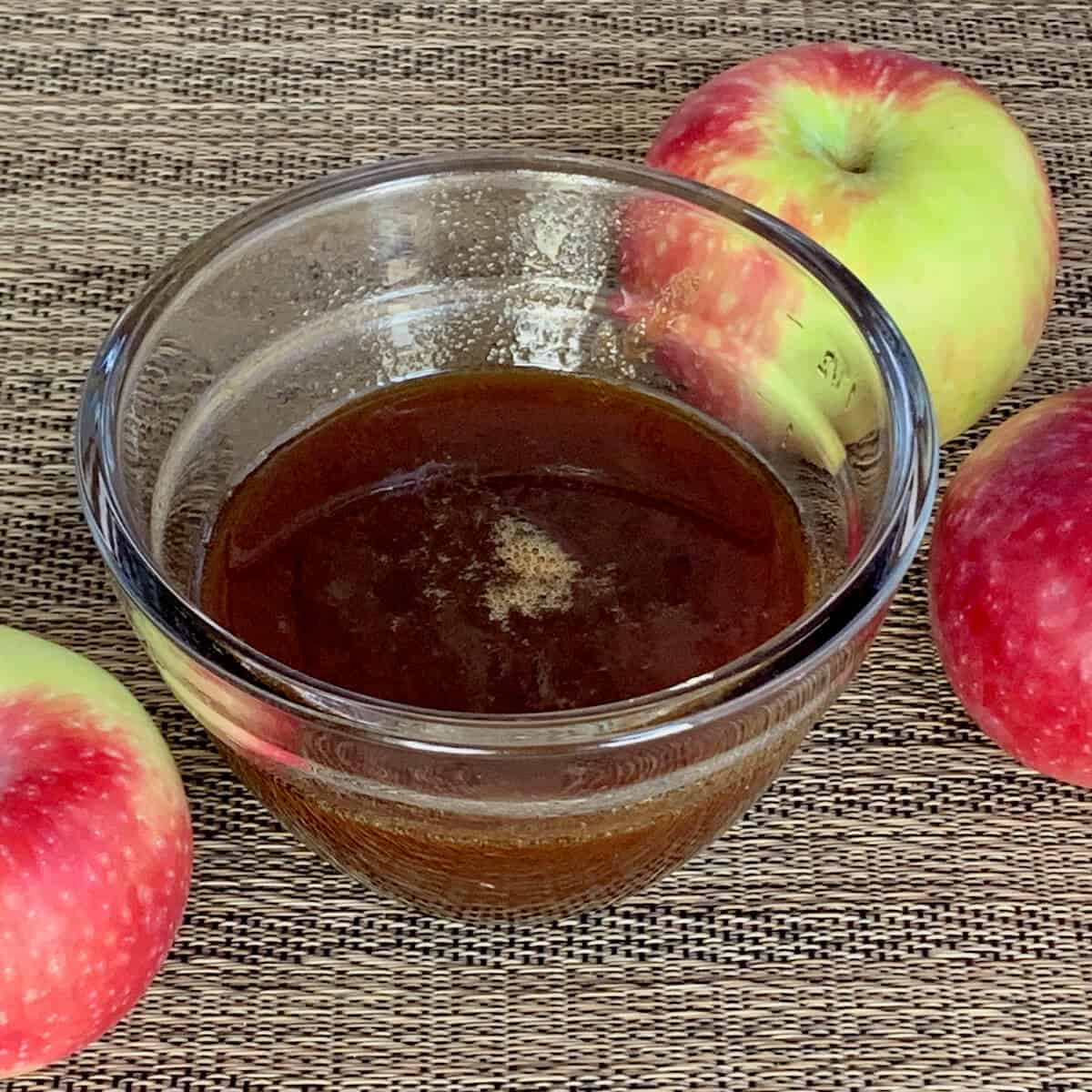Boiled apple cider in a glass bowl with apples.