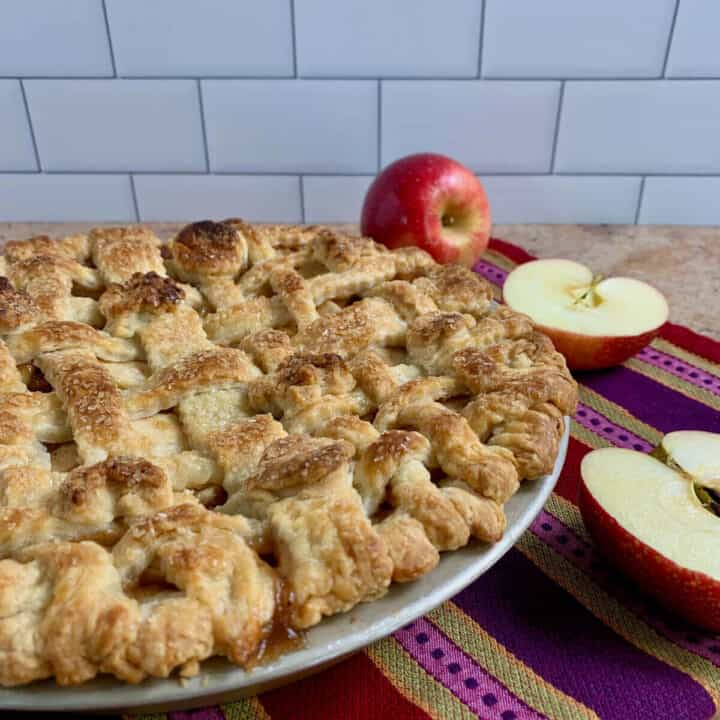 Lattice topped apple pie on a purple striped towel with cut apples.